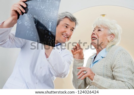 Happy mature male doctor with senior female patient looking at x-ray - stock photo
