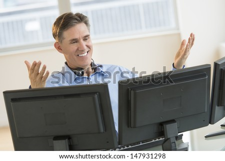 Happy mature male trader gesturing while using multiple screens at desk in office