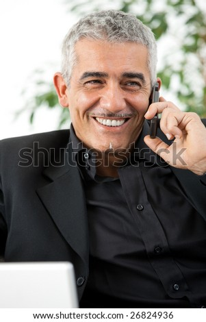 Happy mature man calling on mobile phone, smiling, indoor. - stock photo