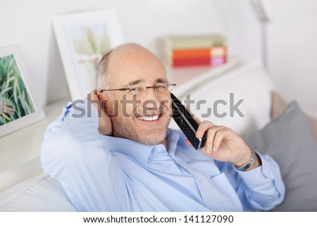 Happy mature man calling on using telephone at home - stock photo