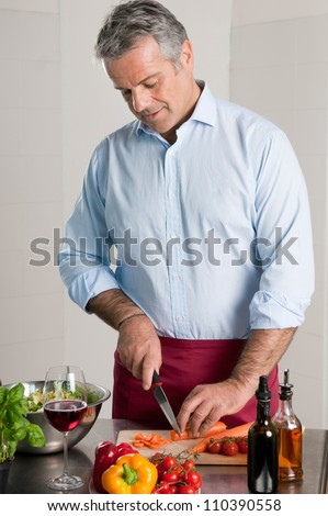 Happy mature man cutting fresh organic carrots for an healthy vegetarian lunch