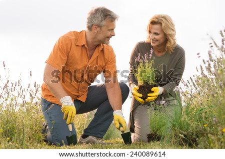 Happy Mature Man Digging In Field And Woman Holding Potted Plant - stock photo