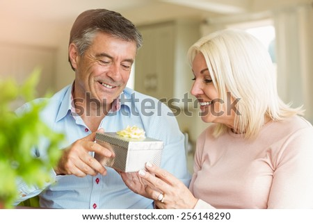 Happy mature man offering wife a gift at home in the kitchen - stock photo