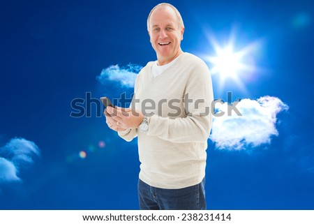 Happy mature man sending a text against bright blue sky with clouds - stock photo