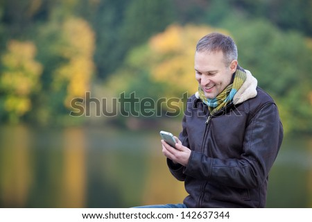 Happy mature man using mobile phone against lake - stock photo