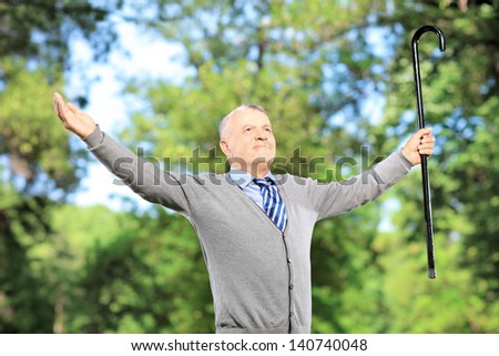 Happy mature man with cane spreading his arms in a park - stock photo
