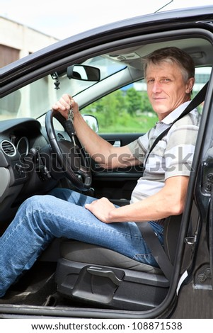 Happy mature man with car key sitting in own land vehicle - stock photo
