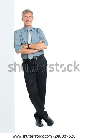 Happy Mature Manager With Arms Crossed Leaning Against Blank Placard Looking At Camera Isolated on White Background - stock photo