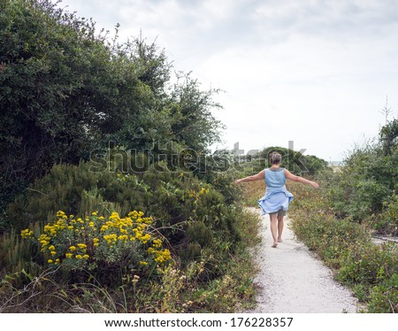Happy mature senior woman looking fit as she walks on sandy path through beach sand dunes with flowering island plants and vegetation.