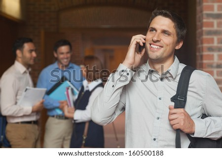 Happy mature student phoning with his smartphone in the corridor - stock photo