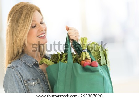 Happy mature woman carrying shopping bag full of vegetables at home