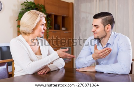 Happy mature woman chatting with young boyfriend indoors