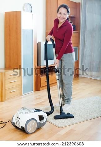 Happy mature woman cleaning with vacuum cleaner   in living room  - stock photo