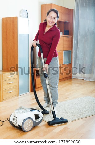 Happy mature woman cleaning with vacuum cleaner on  floor in living room