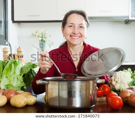 Happy mature woman cooking lent diet soup in  kitchen