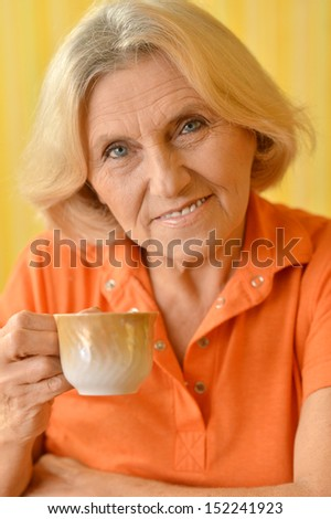 Happy mature woman drinking tea on yellow background