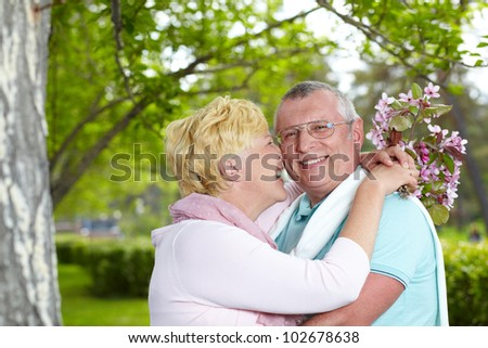 Happy mature woman embracing her husband and touching his cheek by her nose