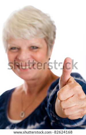 Happy, mature woman giving thumbs up for approval. - stock photo