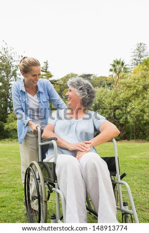 Happy mature woman in wheelchair talking with daughter in the park on sunny day