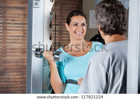Happy mature woman lifting weights while looking at instructor at health club - stock photo