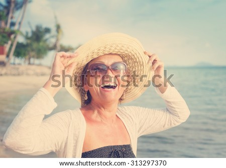 Happy mature woman of 50 years on the beach - stock photo