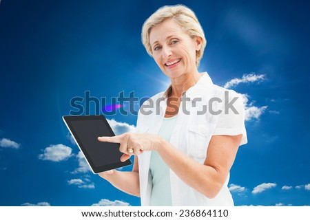 Happy mature woman pointing to tablet pc against cloudy sky with sunshine - stock photo