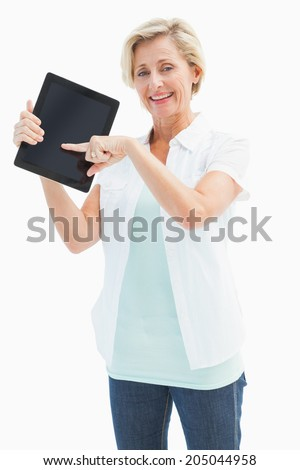 Happy mature woman pointing to tablet pc on white background - stock photo