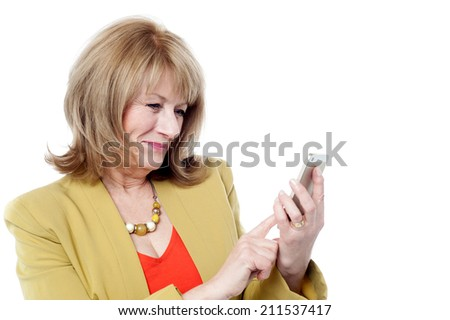 Happy mature woman reading emails on mobile phone