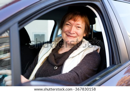 Happy mature woman sitting in new car at driver seat - stock photo