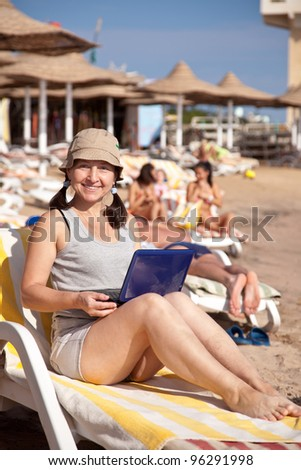 Happy mature woman sitting  with laptop at resort beach - stock photo