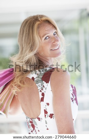 Happy mature woman smiling with shopping bags outdoors - stock photo