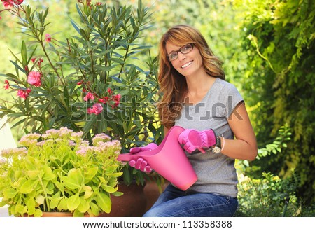 Happy mature woman taking care of her plants ( and watering them ) in her garden