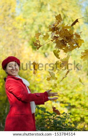 Happy mature woman  throw up maple leaves
