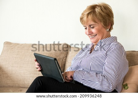 Happy mature woman using a tablet - stock photo