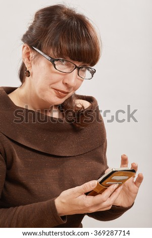 happy mature woman using phone on white background