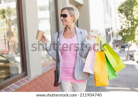 Happy mature woman walking with her shopping purchases on a sunny day - stock photo