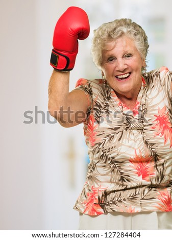 Happy Mature Woman Wearing Boxing Glove, Indoors - stock photo