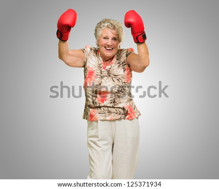 Happy Mature Woman Wearing Boxing Glove On Grey Background - stock photo