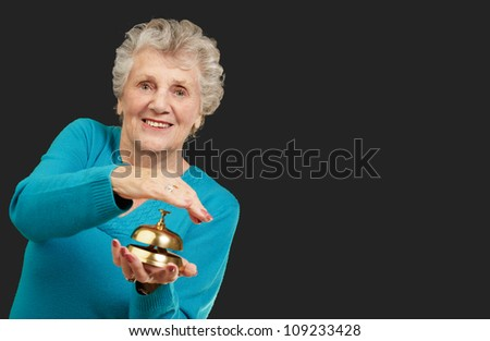 Happy Mature Woman While Holding Bell On Black Background