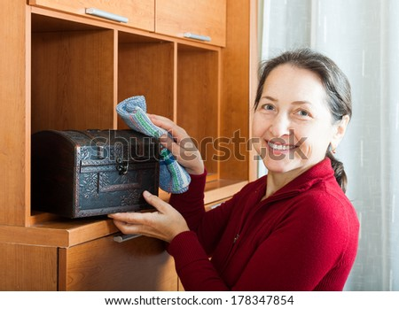 Happy mature woman wiping dust from wooden chest at home
