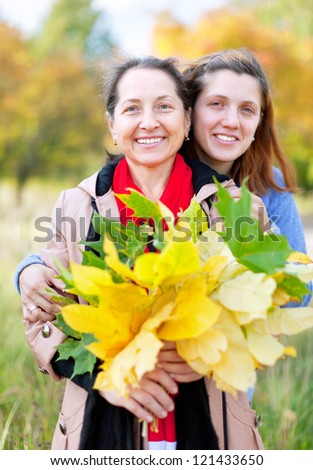 Happy  mature woman with adult daughter in autumn  park - stock photo