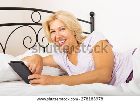 Happy mature woman with eBook laying in  bed at home  - stock photo