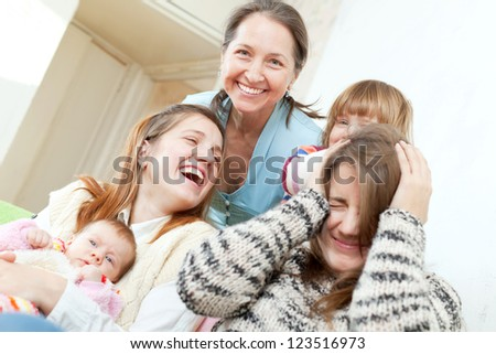 Happy mature woman with her daughters and granddaughters in home