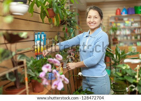 Happy mature woman with  Kalanchoe plant surrounded by different flowers in flower store - stock photo