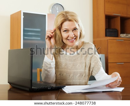 Happy mature woman with laptop and financial documents at table in home or office interior - stock photo