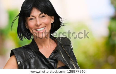 Happy Mature Woman With Short Hair against a nature background - stock photo