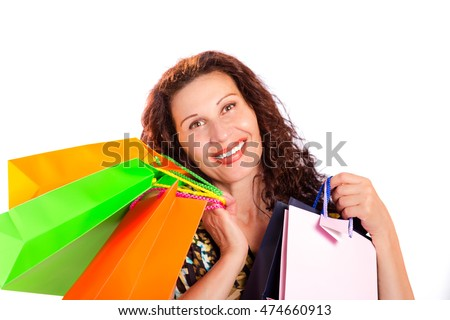 Happy mature woman with wrinkles showing colorful shopping bags isolated on white background