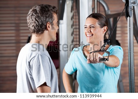 Happy mature woman working out while looking at instructor at health club - stock photo