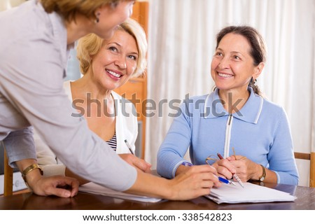 Happy mature women consulting at insurance agent office. Focus on the left woman