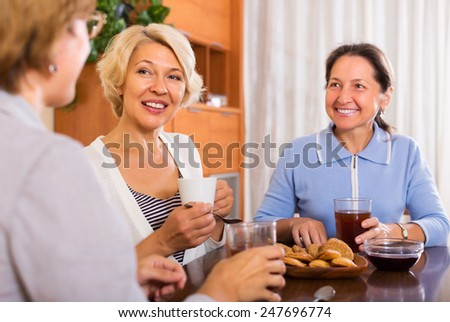 Happy mature women having coffee break at office. Focus on blonde woman - stock photo